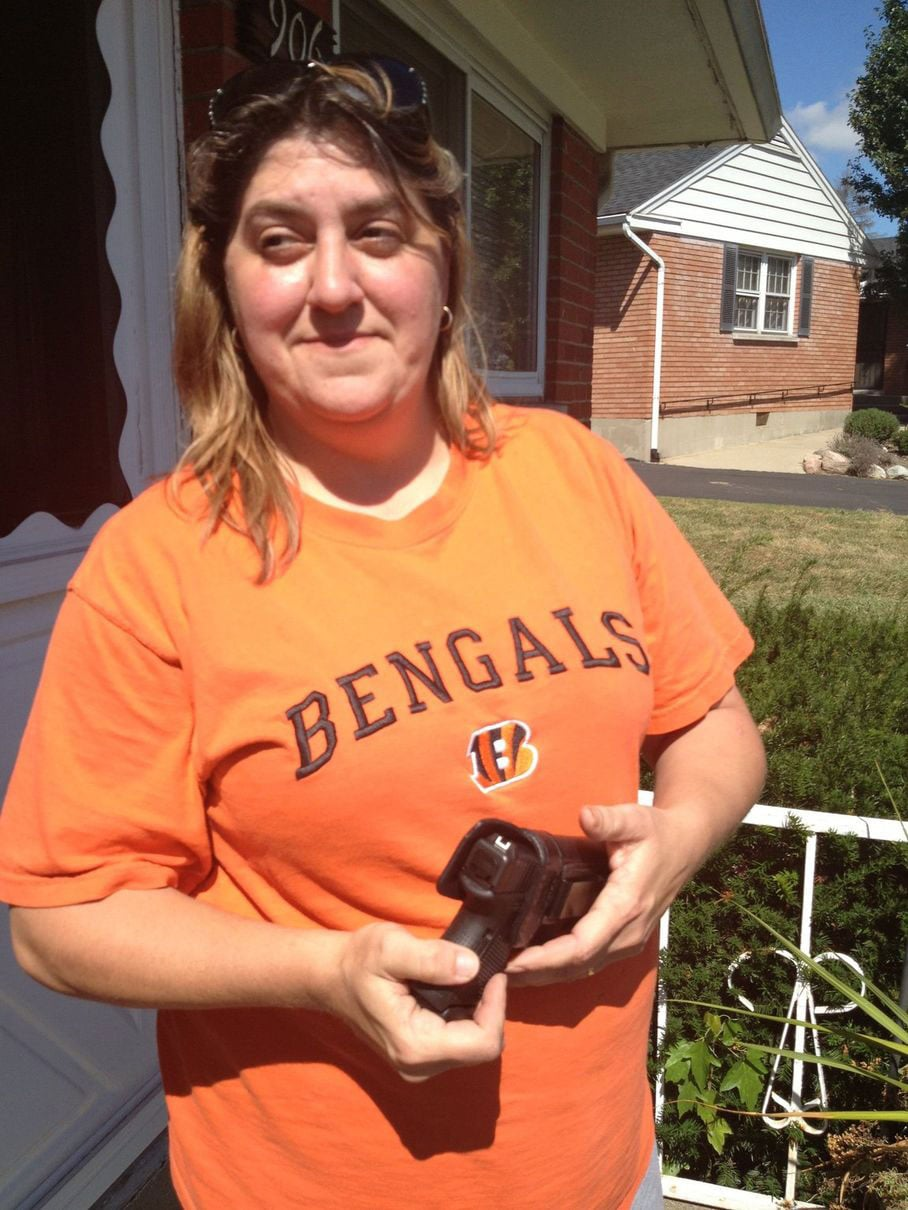 Tonia Smith, Fletcher's proud daughter, shows off the Glock 9mm pistol that her mother used to defend herself. (Photo credit: Middletown Journal)
