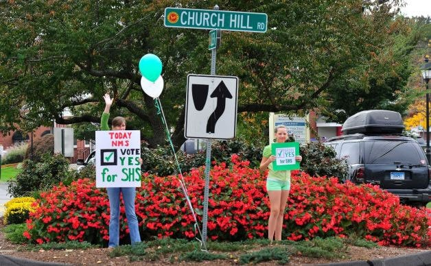 """Newtown residents hold """"Vote Yes"""" signs as people pass on their way to cast votes for the demolition and rebuilding of the Sandy Hook school. (Photo credit: News Times)"""