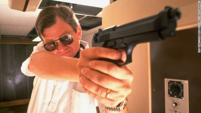 Clancy poses with his pistol during target practice in his private underground pistol range in Maryland in 1989