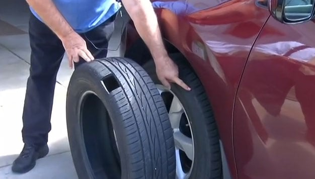 Mike Cardella shows reporters where the .223 round hit his tire. (Photo credit: ABC)