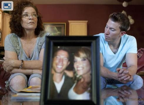 """Pamela Blaies and her son, Jonathan, sit behind a picture of Amanda Blaies-Rinaldi. In 2011, Pamela showed Amanda a domestic violence pamphlet and said, """"Look at this… this is you."""" Amanda told her mother not to worry. Two days later she was dead after her husband shot her twice in the chest and three times in the head. All the signs were there beforehand. (Photo credit: USA Today)"""