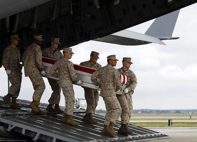 Marines carry the transfer case containing the remains of Marine Lance Cpl. Jeremiah M. Collins Jr., of Milwaukee, Wis., upon arrival at Dover Air Force Base, Del. on Oct. 7. (Photo credit: AP)