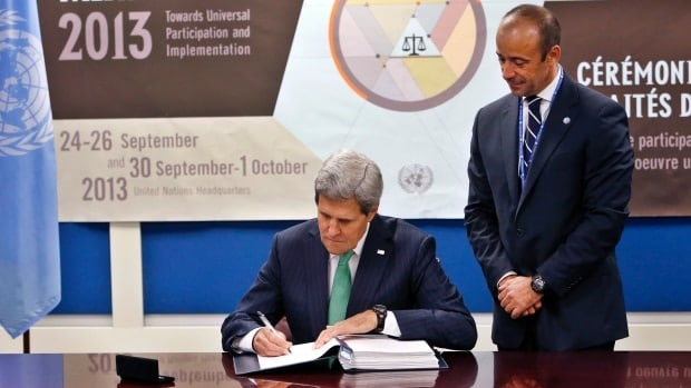 U.S. Secretary of State John Kerry signs the Arms Trade Treaty as Under Secretary-General for Legal Affairs Miguel Serpa Soares looks on. (Photo credit: Associated Press)
