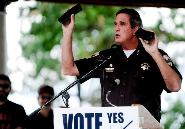 Sheriff Cooke holding up two 30-round magazines.  One was purchased before July 1, the other was not.  Can you tell the difference?