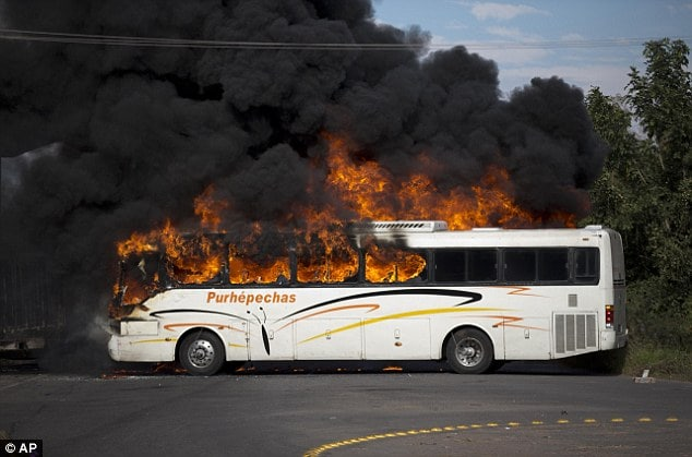 A bus burns at the entrance of Paracuaro, Mexico as residents of villages near Paracuaro set at least six cars and trucks on fire to protest the arrival of more than 100 vigilantes to their town of michoacan