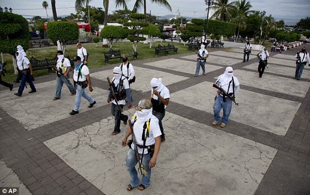 In formation- Self-Defense Council fighters enter the man plaza of the town of Nueva Italia on Sunday