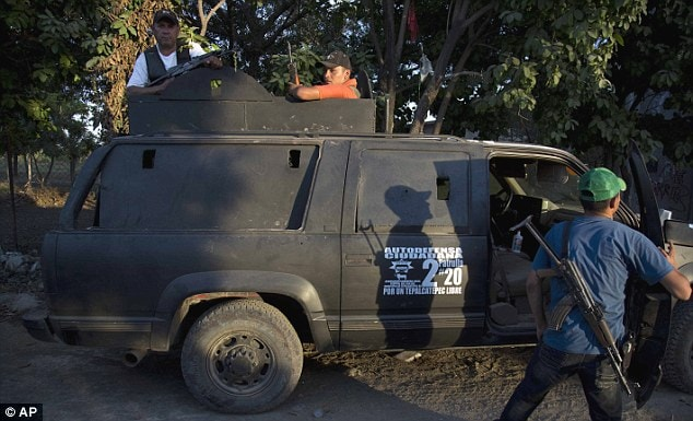 Members of a self-defense group arrive on an armed vehicle to the village of Las Yeguas in Michoacan state