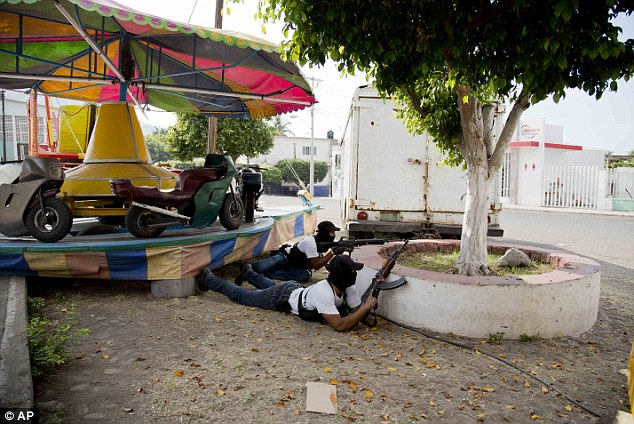 Under cover- Self-Defense Council fighters take cover near a carnival ride in the town of Nueva Italia on Sunday