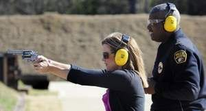 Stephen Lavender teaches Kym Klass how to safely handle a firearm during one of the monthly Firearms Familiarization Courses offered at the Montgomery Police Academy. (Photo credit: Montgomery Advertiser)