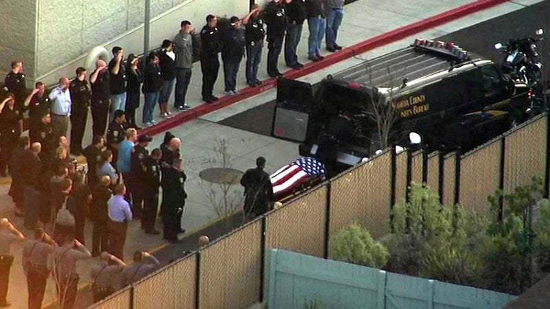 A gurney carrying Smith's body was rolled out of the hospital, draped in an American flag, as fellow officers and others stood saluting, paying respect to the fallen officer. (Photo credit: Mercury News)