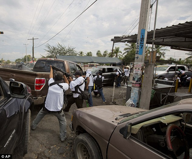 men belonging to the self-defense council of michoacan engage in a firefight while trying to flush out alleged members of the Knigts Templar drug cartel from Nueva Italia on Sunday January 12, 2014