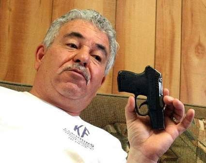 """John Filippidis shows off the Kel-Tec .380 he normally carries. """"Things aren't like they used to be. The break-ins, the burglaries, all the crime… I wanted to be able to defend my family, my household and the ground I'm standing on. But I'm not looking for any trouble,"""" he said. (Photo credit: The Tampa Tribune)"""