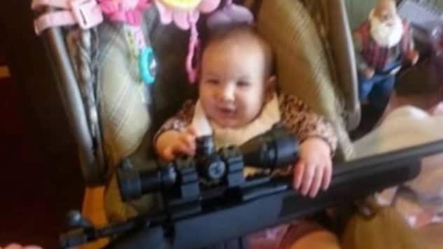 baby holding rifle