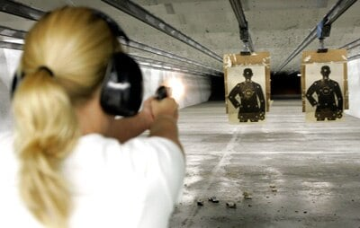 woman shooting at targets indoor range