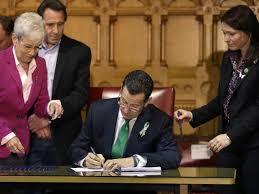 Connecticut Democratic Gov. Dannel Malloy signs gun control legislation at the Capitol on April 4, 2013 (Photo credit: Steven Senne/AP)