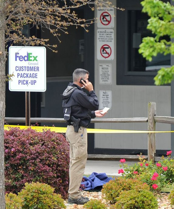 """Though a city ordinance requires every household to have a gun, the FedEx facility was a gun-free zone. The """"no weapons allowed"""" signs posted on the doors were obviously ignored by the suspect. (Photo credit: The Atlanta Journal-Constitution)"""