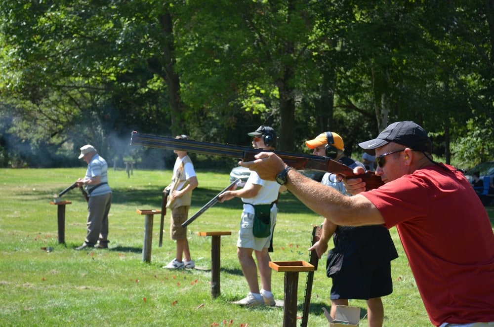 Folks enjoying trap shooting, which is similar to skeet. In trap, discs fly up, down and away, whereas in skeet, discs side to side.