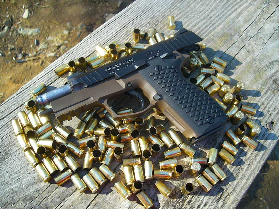 handgun sitting on a table on top of empty bullet casings