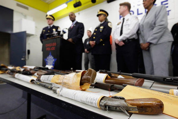 Chicago police officials speak at a news conference with a display of recently seized guns. (Photo credit: M. Spencer Green/AP)