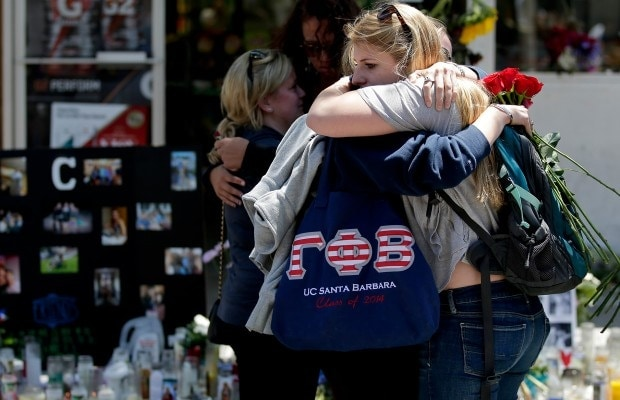 Mourners hug in front of the IV Deli Mart, where part of Friday night's mass shooting took place, in Isla Vista California. (Photo credit: Chris Carlson/AP)