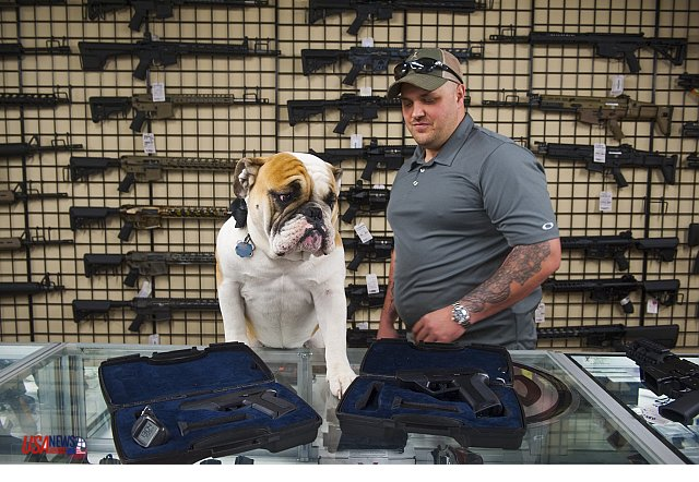 Maryland gun shop owner Andy Raymond, right, recently backpedaled on carrying the Armatix iP1, a .22 caliber smart guns show on counter. (Photo credit: Katherine Frey/The Washington Post)