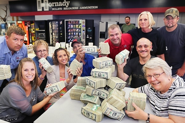 Jason Hornady, vice president of sales and marketing at Hornady Manufacturing, in red, with 30,500 $2 bills and a collection of Hornady employees just before bonuses were issues. (Photo credit: Barrett Stinson/World Herald News Service)
