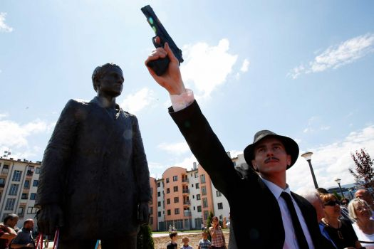 Bosnian actor Jovan Mojsilovic poses with a plastic replica gun during ceremony of unveiling statue of Gavrilo Princip in Sarajevo, on Friday, June 27, 2014. (Photo credit: Amel Emric/AP)