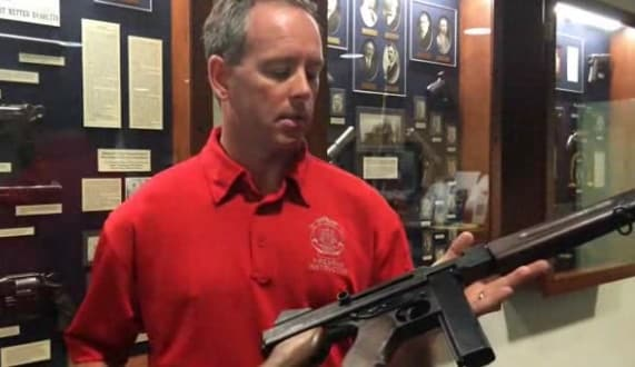 Sgt. Christopher Blake Tucker, a weapons officer with St. Louis Metro Police, shows off one of the department's 30 Thompson submachine guns up for auction. (Photo credit: St Louis Post-Dispatch screen capture)