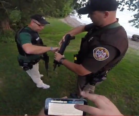 Calumet County sheriff's deputies inspect an open carry advocates AK-style pistol after stopping him while carrying in a local park this weekend. (Photo credit: William Polster)