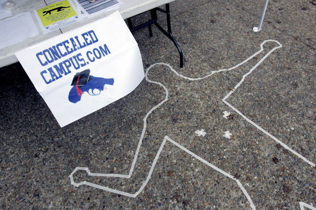 Signs and a replica of a crime scene draw attention to a booth for Students for Concealed Carry, who have filed a lawsuit seeking to allow guns at Ohio State University. (Photo credit: Eric Gay/AP)