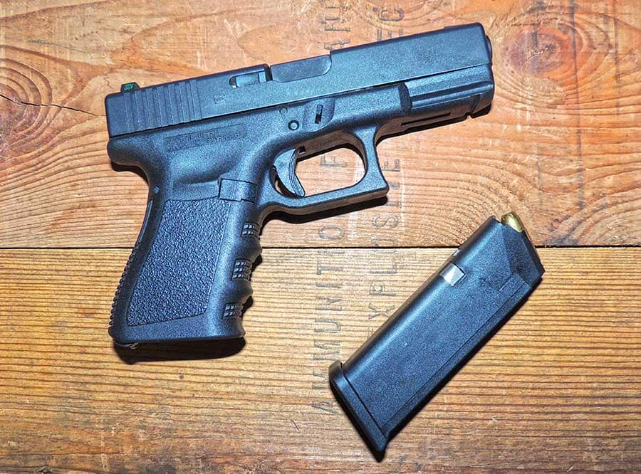 glock 19 with 15 round magazine on wooden table