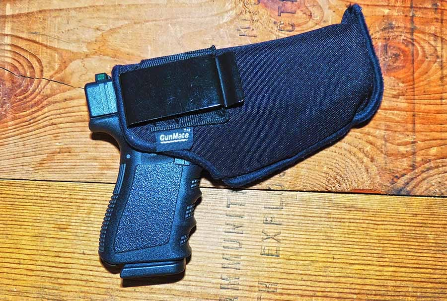 glock 19 concealed in holster on wooden table