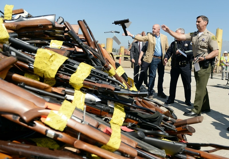Representatives of 12 California law enforcement agencies throw confiscated guns into a pile of among 4700 that were destroyed in the 21st Annual Gun Melt this week. (Photo: Will Lester/Inland Valley Daily Bulletin)