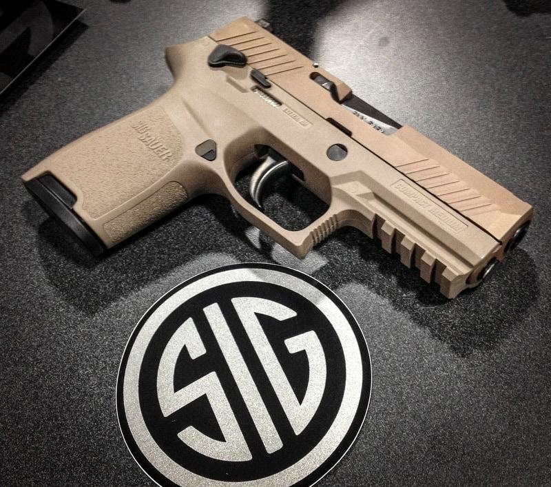 sig p230 handgun next to sig sauer patch
