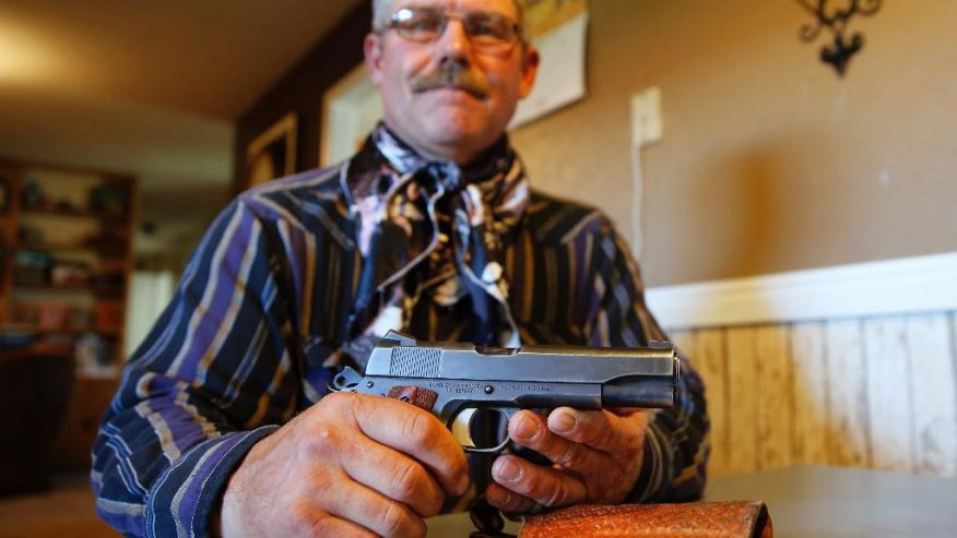An investigator for the Wyoming Livestock Board poses with the M1911A1 he received through a Department of Defense surplus program.