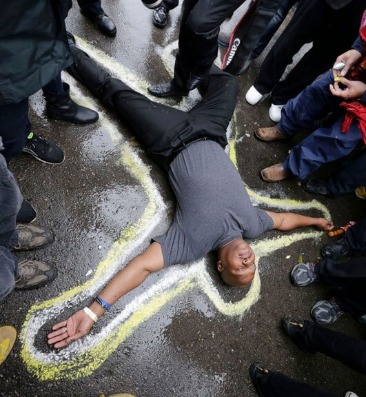 Protesters made a chalk outline of a body outside the Ferguson Police Department as a memorial to Michael Brown