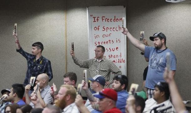 Open Carry Tarrant County members hold up copies of the U.S. Constitution during an Arlington City Council meeting earlier this year. The group won a previous suit in federal court over the city's sidewalk ordinance and is promising a return should a new one be adopted. (Photo: Fort Worth Star-Telegram)