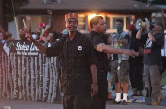 """Believed New Black Panther activist Olajuwon Davis, a/k/a """"Olajuwon Ali"""" and """"Brother Ali,"""" with mustache, seen directing traffic in absence of police during a Ferguson area protest following the death of Michael Brown. (Photo: Danny Wicentowski/Riverfront Times)"""