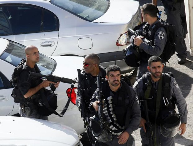 Israeli security personnel walk outside a synagogue that was the scene of an axe attack in the Har Nof neighborhood of Jerusalem, on Nov. 18, 2014. (Photo: AFP)