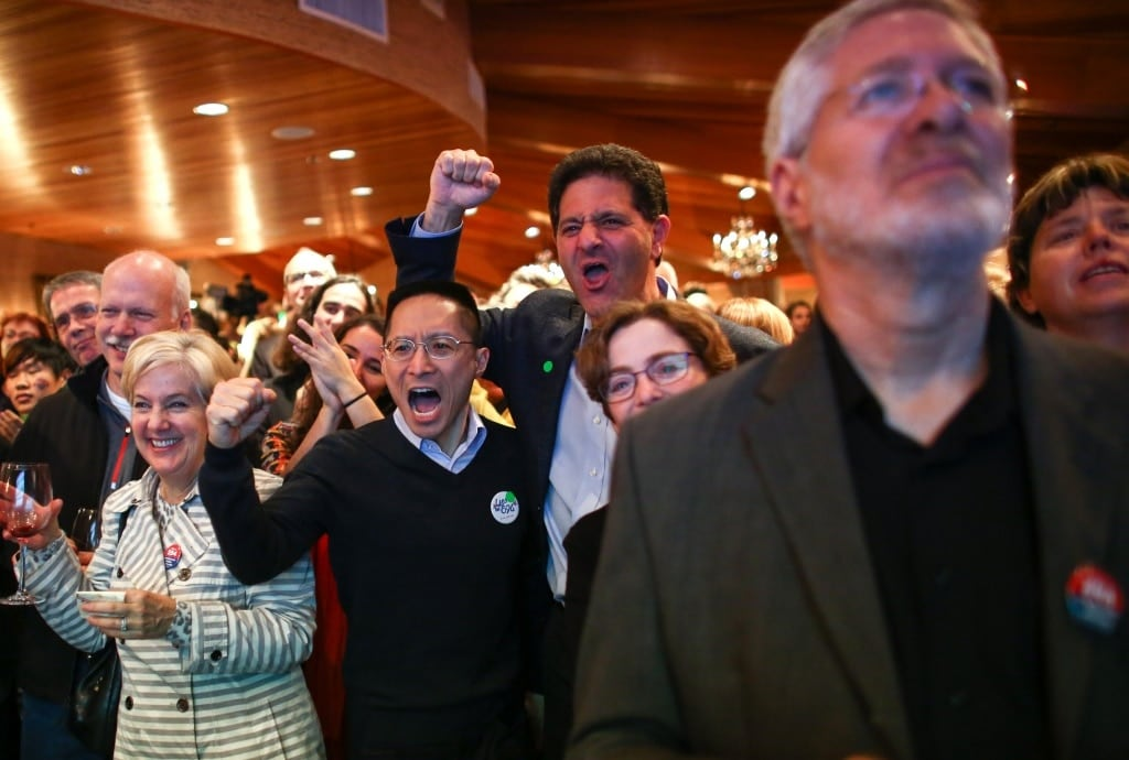 Nick Hanauer, center, who helped back Initiative 594 to the tune of nearly $2 billion, cheers with others during an Initiative 594 return watching party at the Edgewater Hotel in Seattle. (Photo: seattlepi.com)
