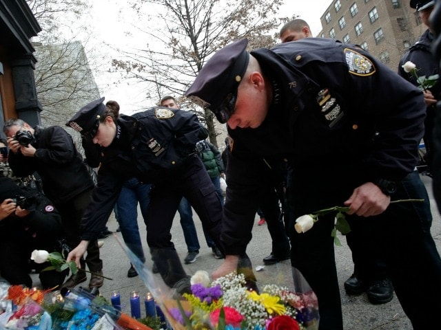 NYPD officers lay flowers near where fellow officers Rafael Ramos and Wenjian Liuby were ambushed by a gunman with a criminal record last weekend. The attack has quickly led to calls for more gun control. (Photo: AP/Mark Lennihan)