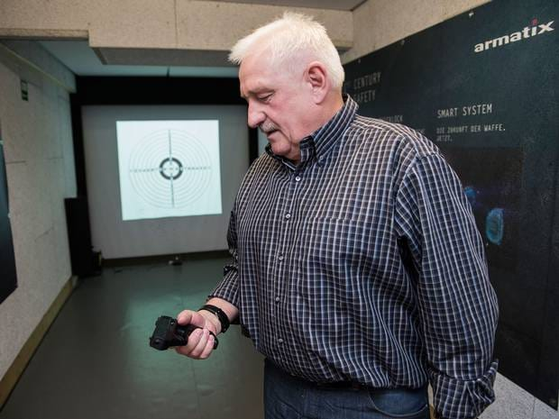 Ernst Mauch examines one of his iP1 personalized digital handguns that will not fire without its companion watch. He plans to market a new 9mm version to U.S. police in 2015. (Photo: Washington Post)