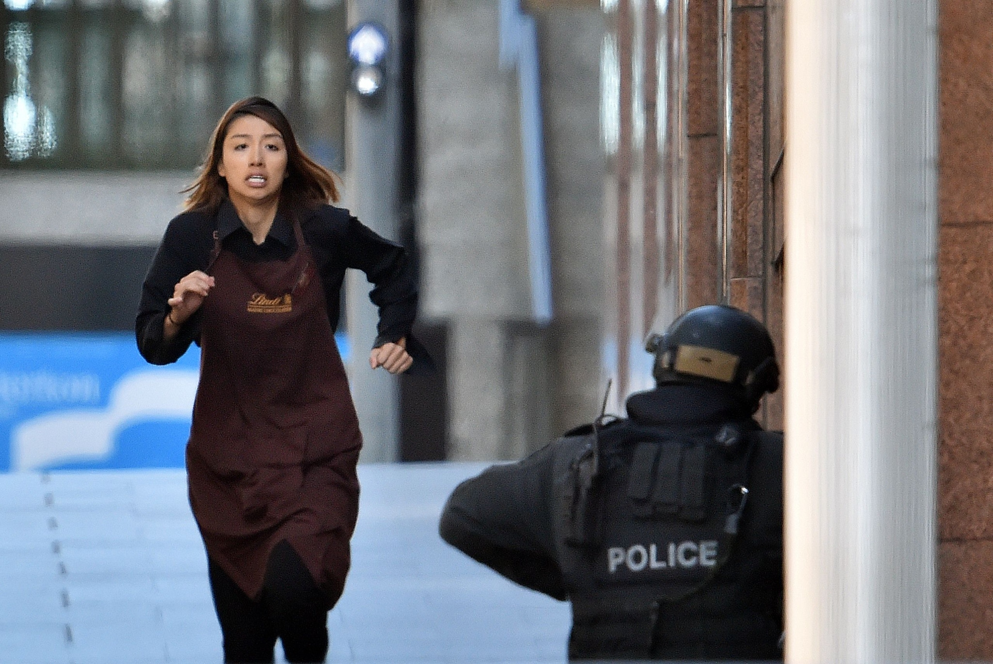A hostage runs from the scene of the Lindt cafe in Sydney Tuesday during standoff with a gunman that resulted in three killed and four injured. (Photo: AFP/Saeed Khan)