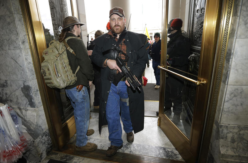 Jason McMillon carries his AR-15 pattern pistol into the Legislative Building at the Capitol in Olympia