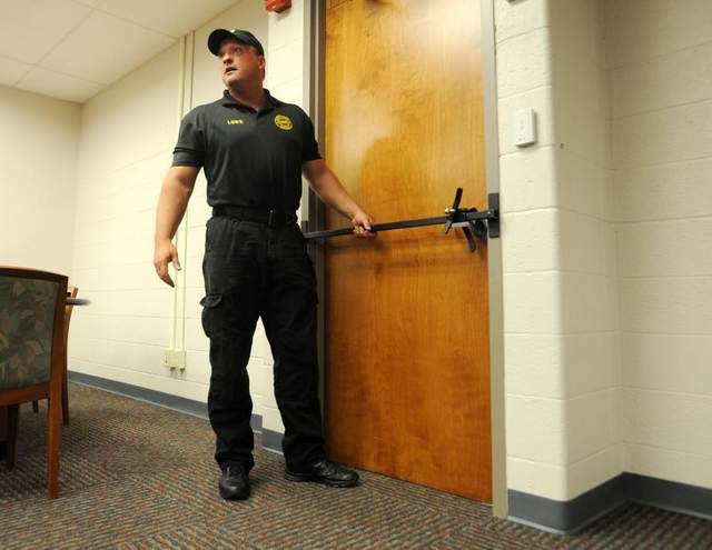 Tony Lowe demonstrates how the Barracuda intrusion prevention device works on outward-opening doors. (Photo: AP)