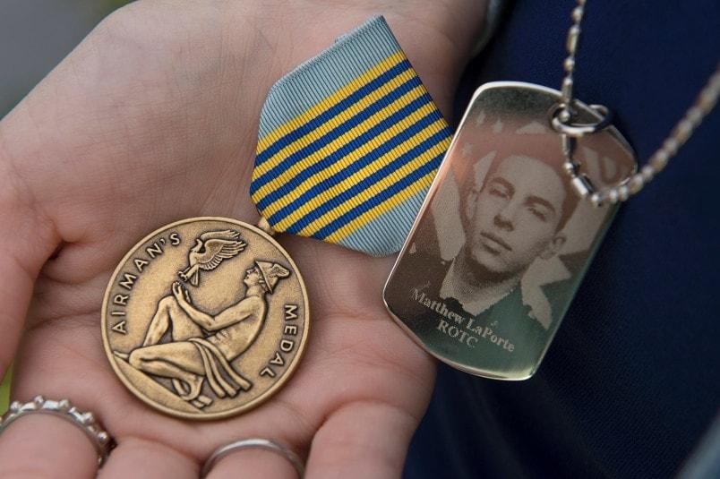 Air Force Cadet Matthew La Porte's Airman's Medal is the palm of his sister's hand April 9, 2015. (Photo: Logan Wallace/VT News https://www.vtnews.vt.edu/photo-galleries/2015/041015-laporte/gallery.html )