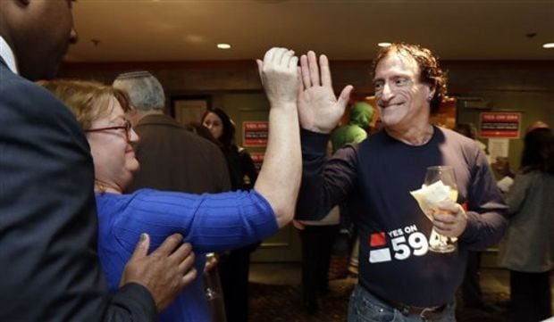 Gun control advocate Cheryl Stumbo, left, celebrates the passage of I-594 last November. She was added as a defendant to a lawsuit by Second Amendment groups that was dismissed this week. (Photo: AP/Elaine Thompson)