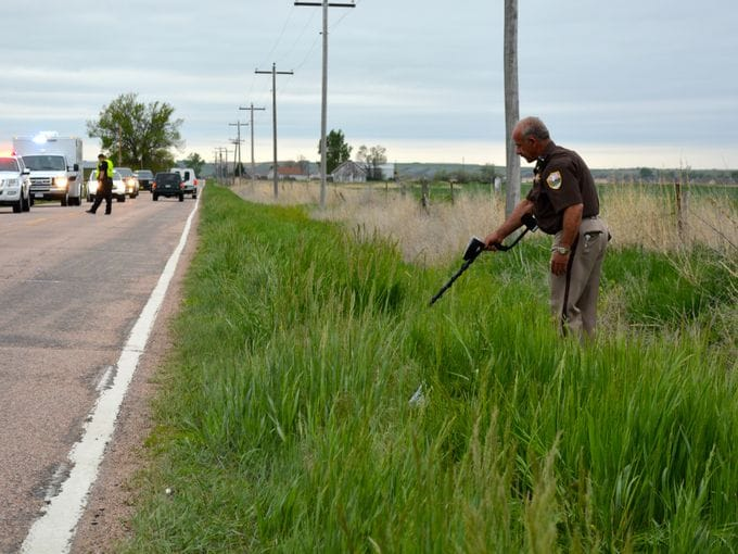 A Weld County Deputy searches the roadside near where 48-year-old bicyclist John Jacoby was shot and killed this week. (Photo: Erin Hull/The Coloradoan)
