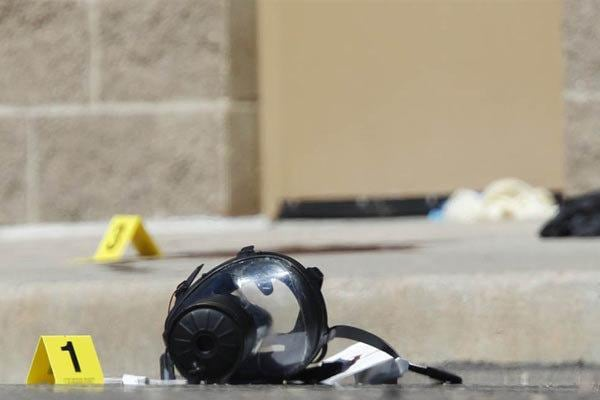 A gas mask marked as evidence sits on the sidewalk outside the Century 16 movie theater.