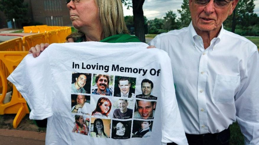 Lonnie and Sandy Phillips, whose daughter Jessica Ghawi was killed in the 2012 Aurora movie theatre massacre, talk with members of the media and display a T-shirt memorializing the twelve people killed in the attack, outside the Arapahoe County District Court following the day of closing arguments in the trial of theater shootings defendant James Holmes, in Centennial, Colo., Tuesday July 14, 2015. (The Associated Press)